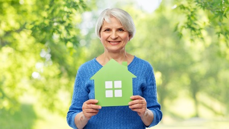 home, environment and ecology concept - portrait of smiling senior woman holding green house icon over natural background