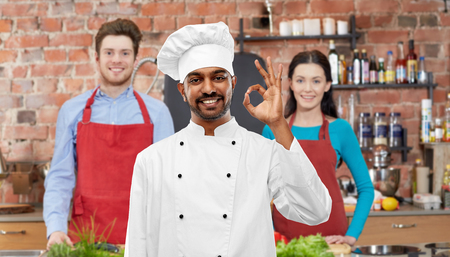 cooking class, profession and people concept - happy male indian chef in toque showing ok gesture over students background