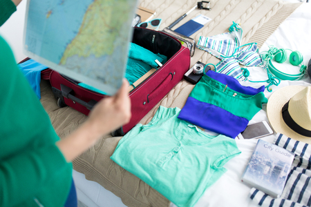 tourism, people and luggage concept - close up of young woman with map packing travel bag at home or hotel room