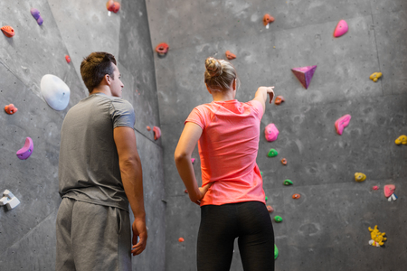 fitness, extreme sport and bouldering concept - man and woman exercising at indoor climbing gym Reklamní fotografie
