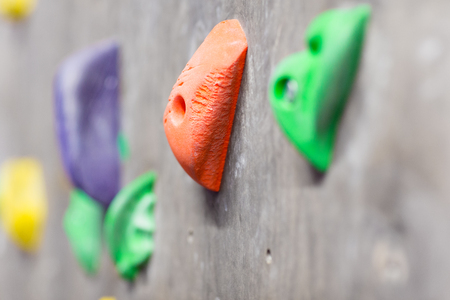 fitness, extreme sport, bouldering, people and healthy lifestyle concept - close up of rock holder on indoor climbing wall