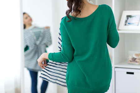 clothing, fashion and people concept - close up of woman choosing clothes at home mirror Reklamní fotografie
