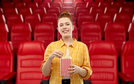 Kino-, Fast-Food- und Unterhaltungskonzept - lächelndes rothaariges Teenager-Mädchen in kariertem Hemd, das Popcorn aus gestreiftem Eimer über Kinohintergrund isst