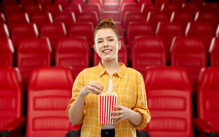 koncepcja kina, fast foodów i rozrywki - uśmiechnięta rudowłosa nastolatka w kraciastej koszuli je popcorn z pasiastego wiadra na tle kina