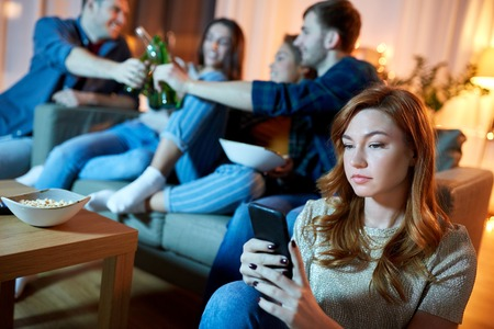 technology, internet addiction and people concept - sad young woman with smartphone at home friends party in evening Stock Photo