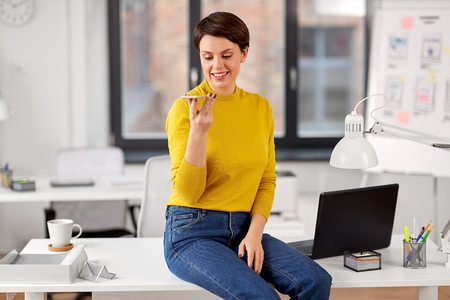 business, technology and people concept - happy smiling businesswoman using voice command recorder on smartphone and sitting on desk at office