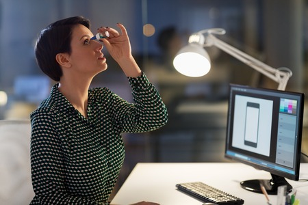 business, vision and overwork concept - female graphic designer with dry eye syndrome using drops at night office