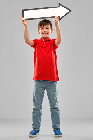 boy holding big white rightwards thick arrow Stok Fotoğraf