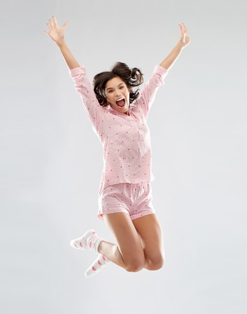 happy woman in pajama jumping high
