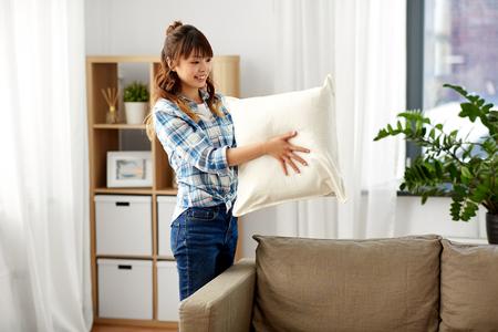 donna asiatica che sistema i cuscini del divano a casa Archivio Fotografico