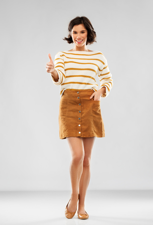 woman in pullover, skirt and shoes shows thumbs up