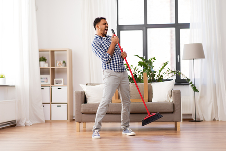 man with broom cleaning and singing at home