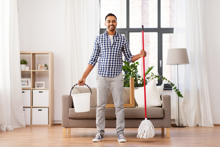 indian man with mop and bucket cleaning at home Stock Photo