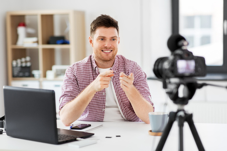 male blogger with camera videoblogging at home Stock Photo