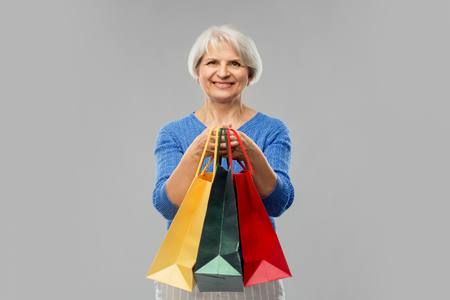 senior woman with shopping bags over grey Stok Fotoğraf