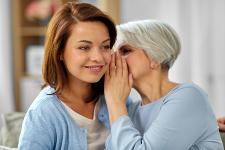 senior mother whispering to adult daughter at home Foto de archivo