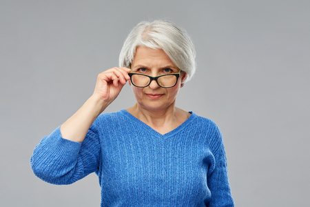 portrait of senior woman looking above glasses