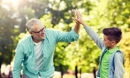 Alter Mann und Junge machen High Five im Sommerpark