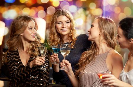 szczęśliwe kobiety stukają się okularami w klubie nocnym