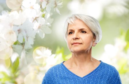 ritratto di donna anziana in maglione blu su grigio Archivio Fotografico