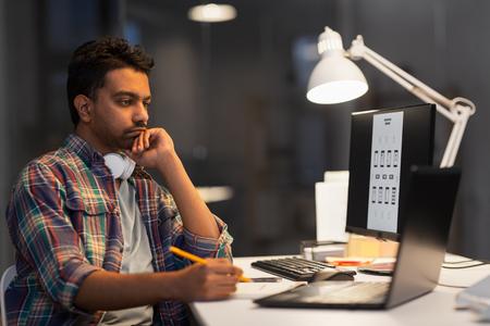 kreativer Mann mit Laptop, der am Nachtbüro arbeitet Standard-Bild