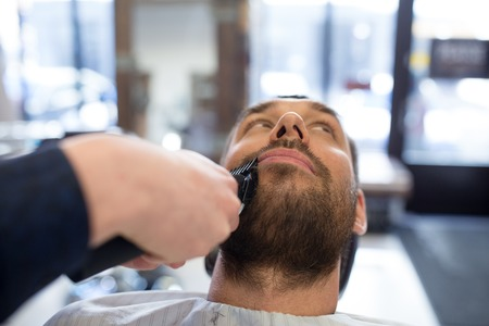man and barber with trimmer cutting beard at salon Stockfoto