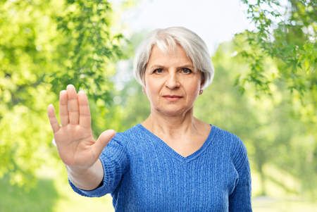 senior woman in blue sweater making stop gesture