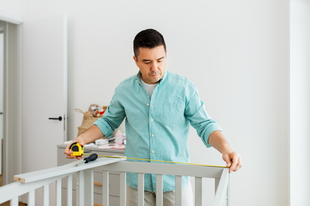 father with tablet pc and ruler measuring baby bed