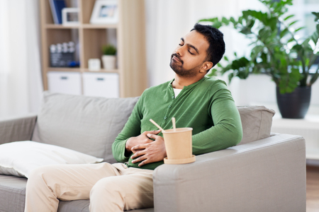 pleased indian man eating takeaway food at home Stock Photo