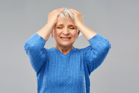 stressed senior woman holding to her head 스톡 콘텐츠