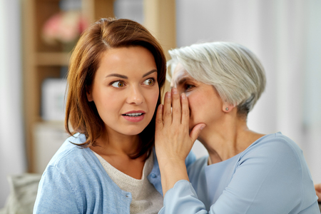 senior mother whispering to adult daughter at home Stock Photo