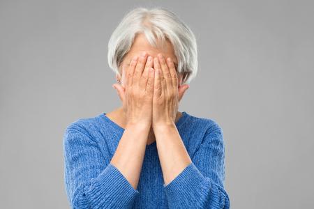 Une femme âgée stressée se couvre le visage avec les mains