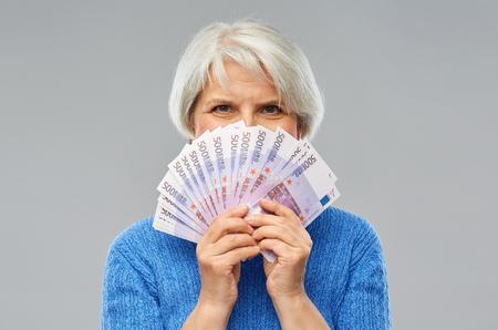 Senior woman with hundreds of euro money banknotes Фото со стока