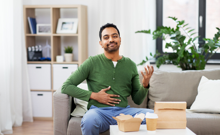 Pleased Indian man eating takeaway food at home