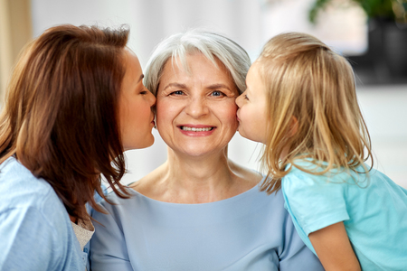 Mother and daughter kissing happy grandmother