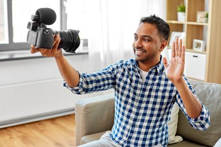 Male video blogger with camera blogging at home Banco de Imagens