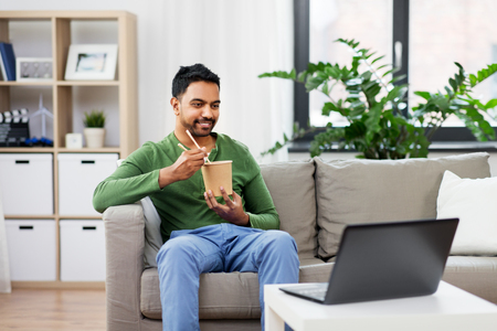 Indian man with laptop eating takeout food at home Stock Photo