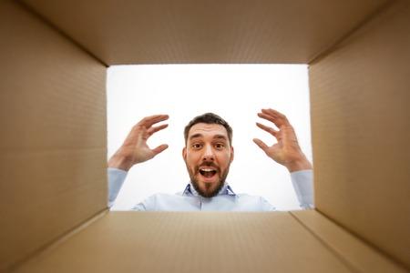Happy surprised man looking into open parcel box 版權商用圖片