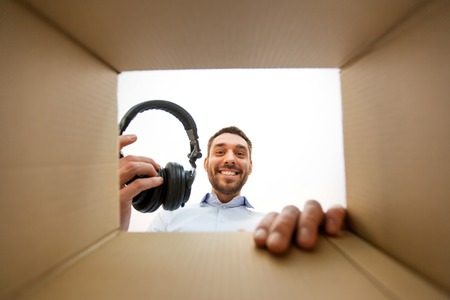 Smiling man taking headphones out of parcel box 版權商用圖片