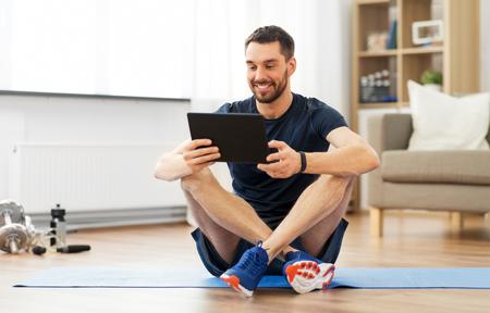 Man met tabletcomputer op oefenmat thuis