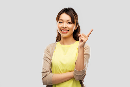 Happy Asian woman pointing finger up 写真素材 - 123604429