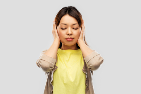 Asian woman closing ears by hands