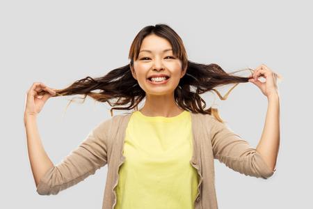 Happy Asian woman with waving hair Banco de Imagens