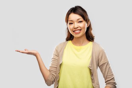 Heureuse femme asiatique tenant quelque chose à portée de main Banque d'images