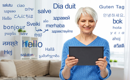 senior woman using translator on tablet computer Stockfoto