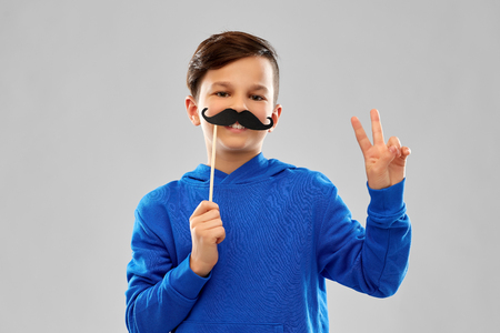 lächelnder Junge im blauen Hoodie mit schwarzen Schnurrbärten
