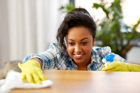 african american woman cleaning table at home