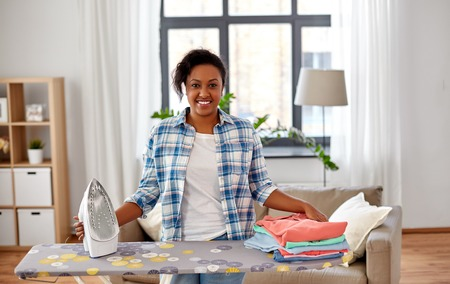 african american woman with ironed clothes at home