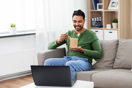 indian man with laptop eating takeout food at home