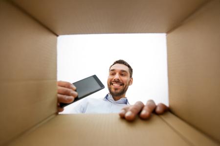 smiling man taking smartphone out parcel box 版權商用圖片